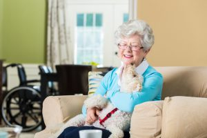 Senior woman hold therapy dog at home